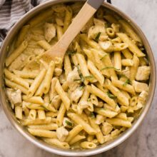 overhead image of chicken pesto pasta in skillet with wooden spoon