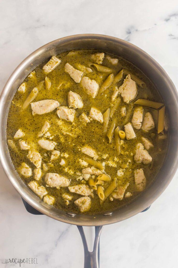 chicken pesto pasta cooking in steel skillet