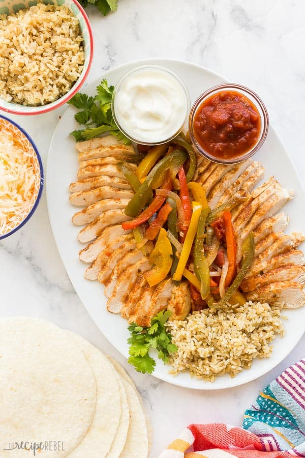 crockpot chicken fajitas on white platter overhead with sour cream and salsa
