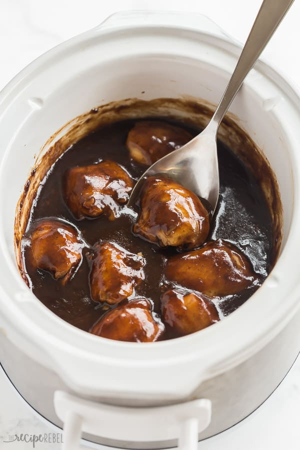 crockpot chicken thighs in slow cooker with thick balsamic glaze and metal spoon