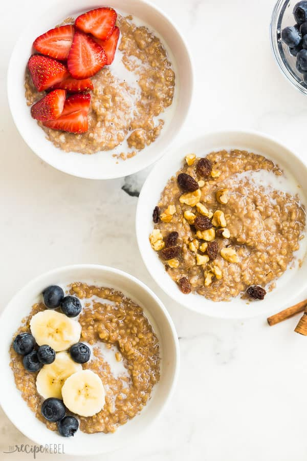 Instant pot oatmeal overhead in three white bowls with berries and nuts