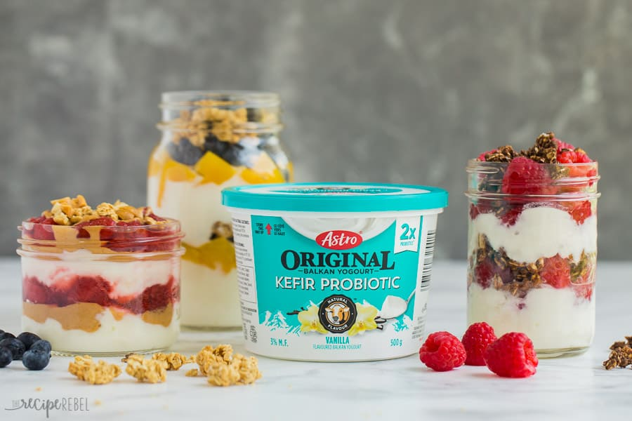 three yogurt parfaits with kefir yogurt container in middle
