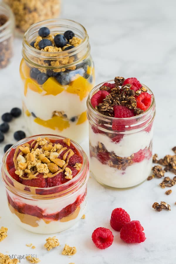yogurt parfait in glass jars on white background with freseh berries, granola, peaches