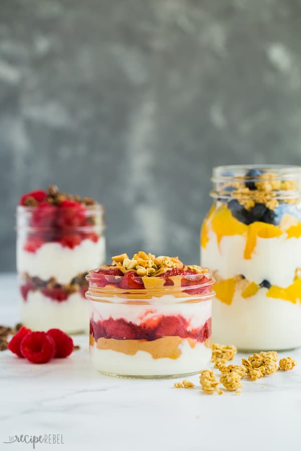 yogurt parfaits in glass jars of varying sizes with fresh fruit and granola