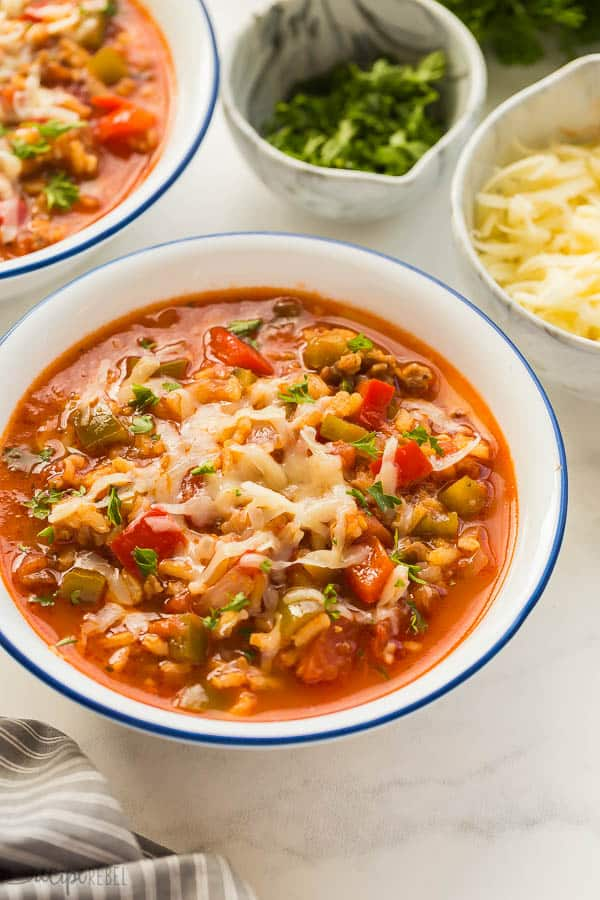 stuffed pepper soup in white bowl close up with shredded cheese