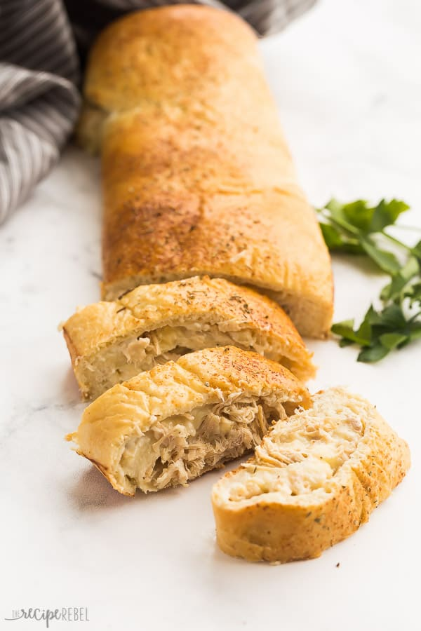 turkey alfredo stromboli sliced with grey towel and fresh parsley in the background