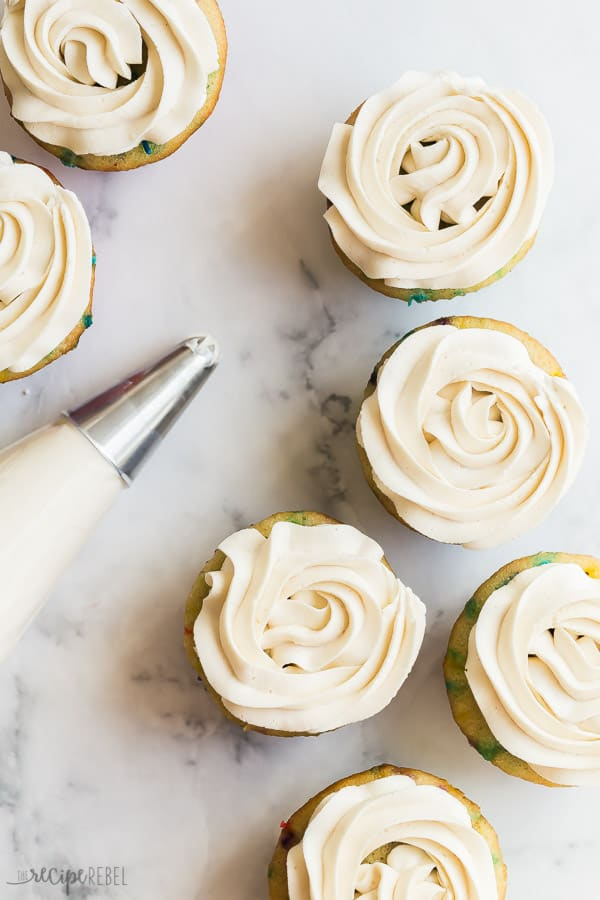 buttercream frosting on cupcakes overhead on marble background