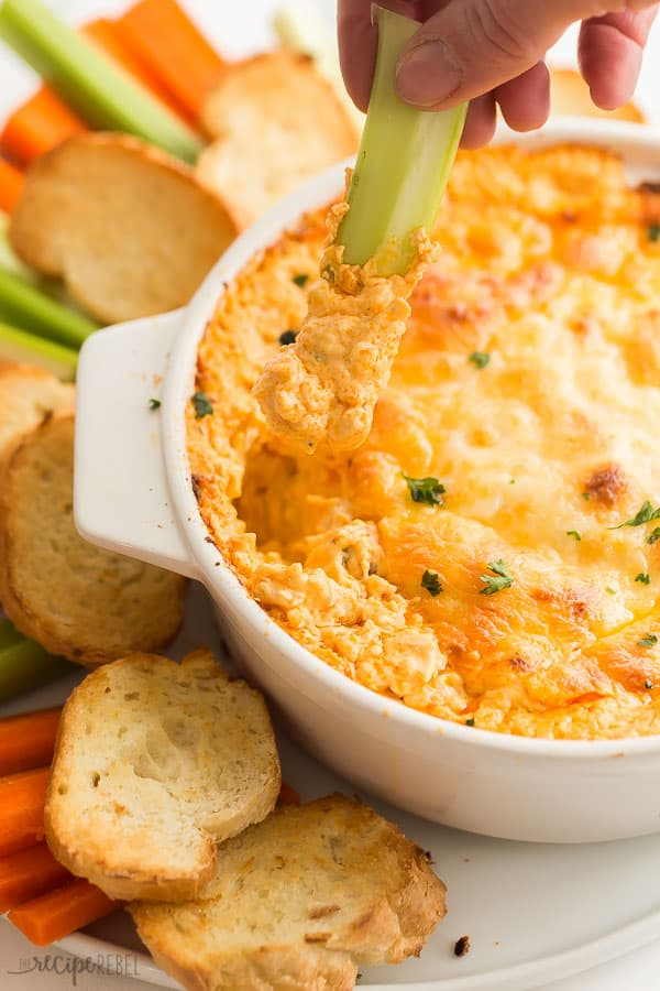 buffalo chicken dip being scooped with piece of celery close up