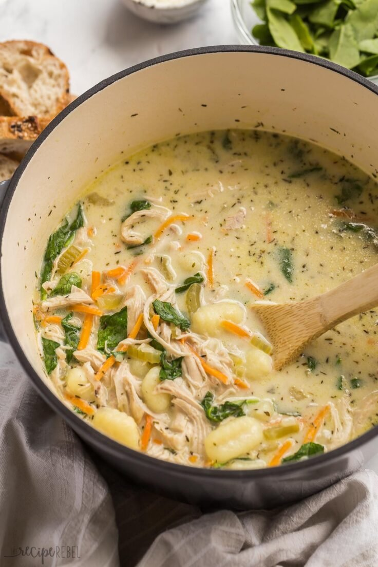 close up image of wooden spoon stirring chicken gnocchi soup