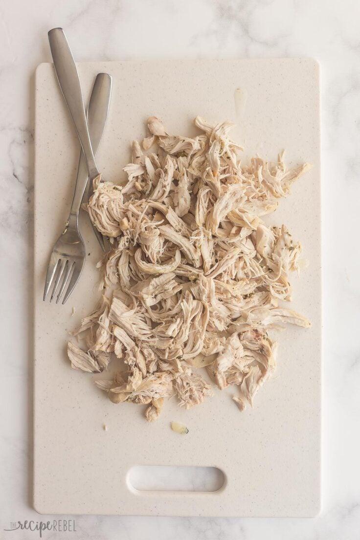 chicken breasts shredded on cutting board