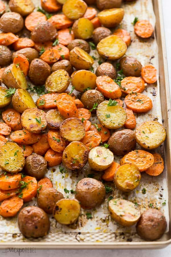 roasted potatoes and carrots on pan with parchment paper
