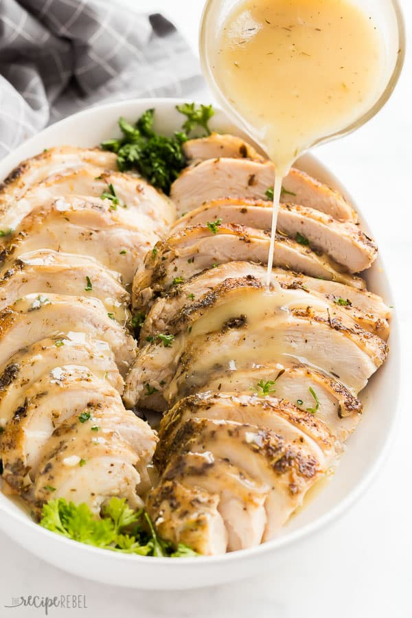 sous vide turkey with gravy in white serving plate with parsley on white background