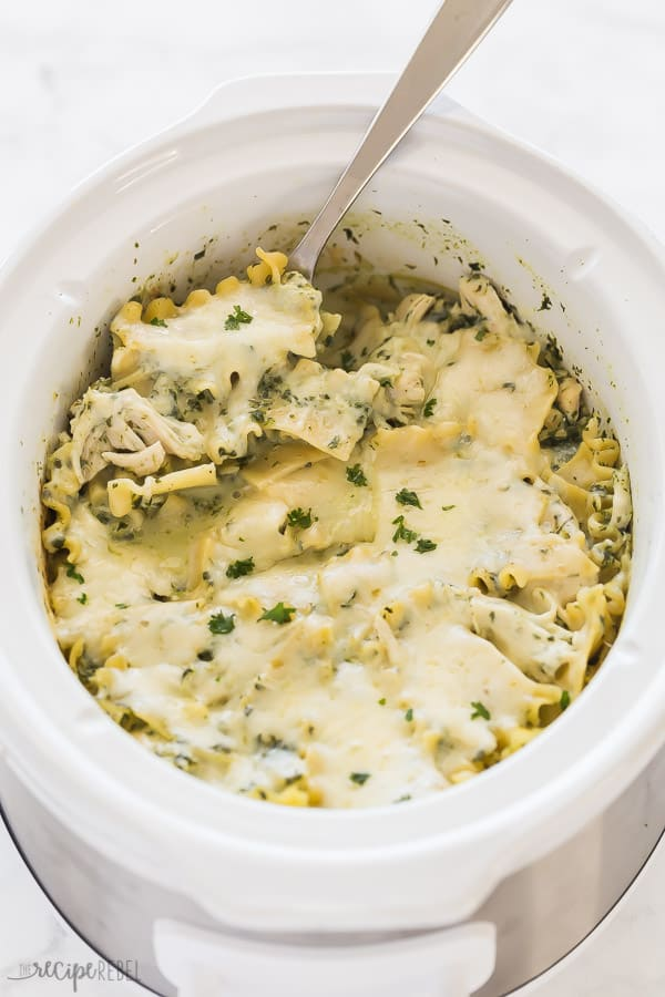 crockpot white chicken lasagna in slow cooker with metal spoon on white background