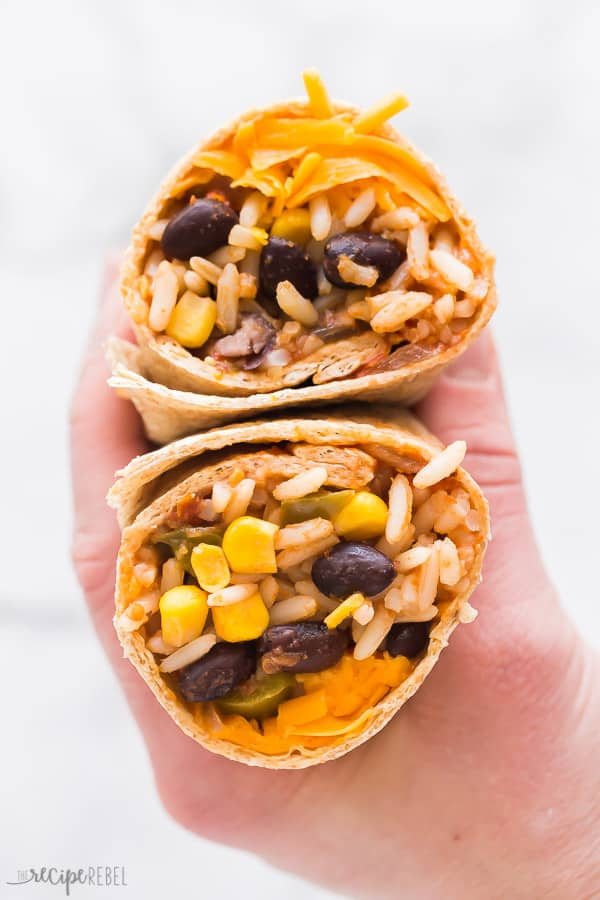 slow cooker vegetarian burrito wrapped with hand holding it