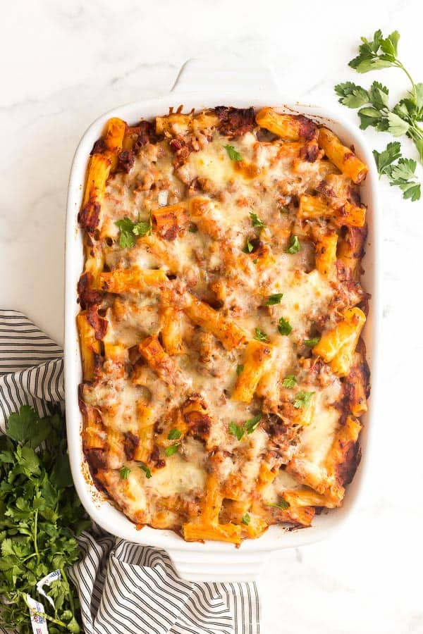 baked ziti with italian sausage in white casserole dish with fresh parsley