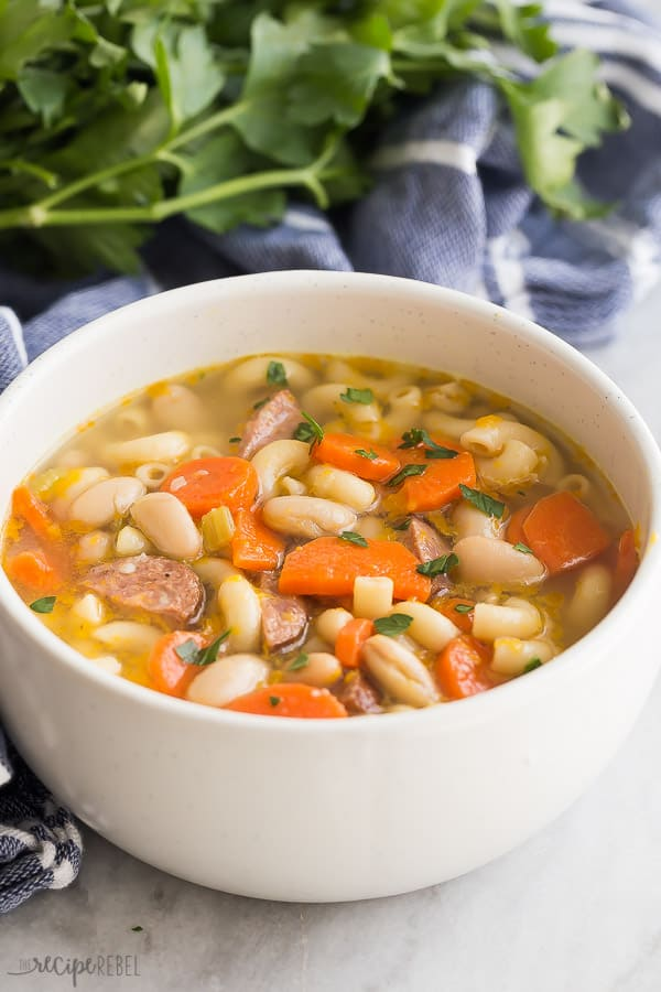 smoked sausage minestrone in a bowl with blue towel and parsley in the background
