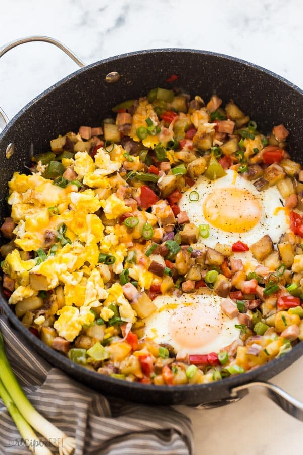 breakfast skillet potatoes and eggs with vegetables in large black pan