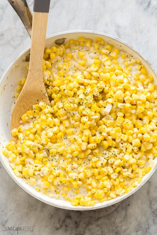 creamed corn overhead in white pan on marble