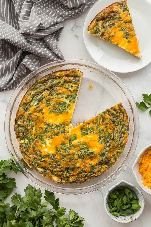 crustless quiche slice out of glass pan with grey towel and parsley