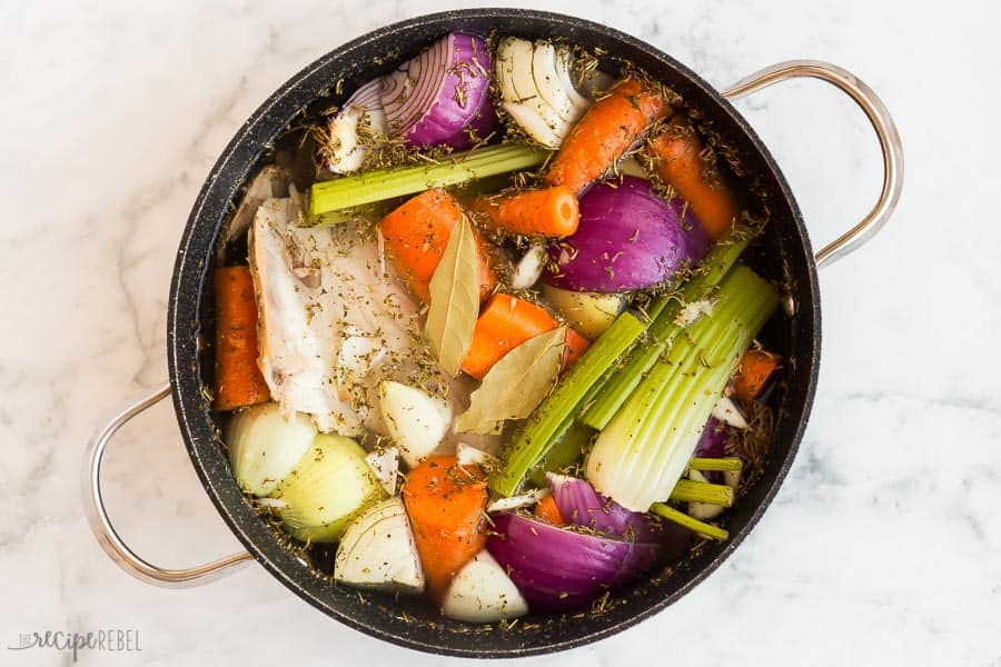 turkey stock with vegetables in black pot overhead on marble