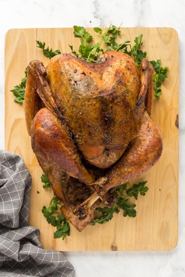 garlic brown sugar dry brine turkey whole on wood cutting board with grey towel