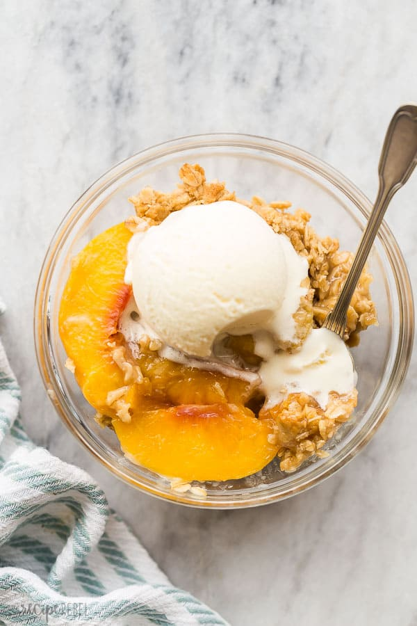peach crisp in bowl overhead on marble background