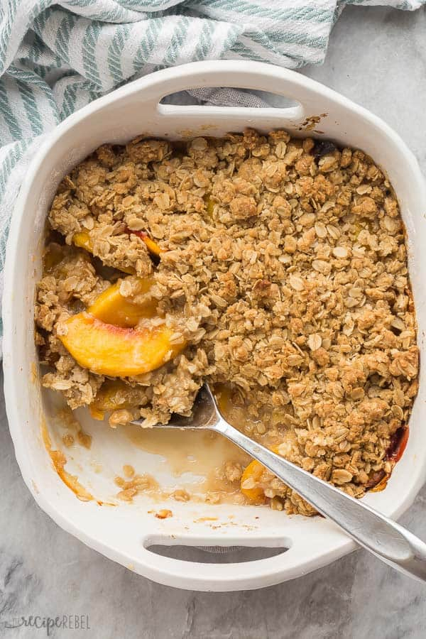 peach crisp in white baking dish overhead with scoop out