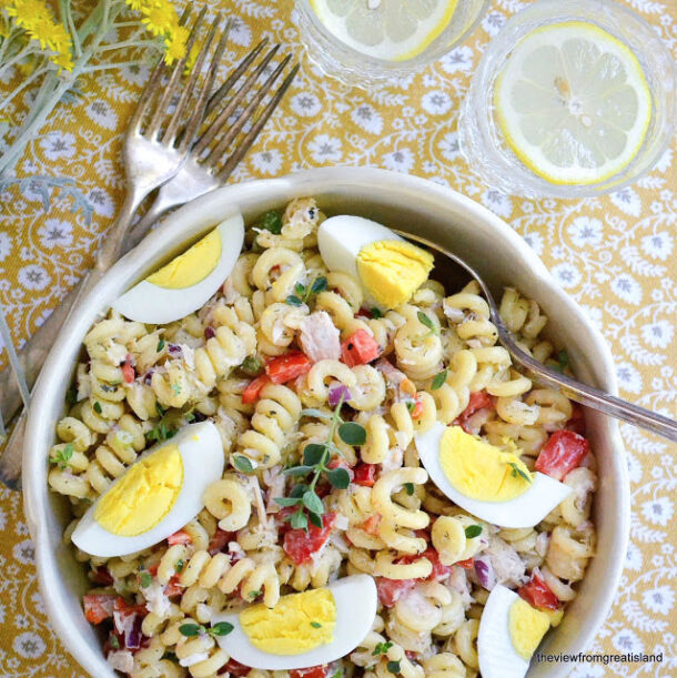 pasta salad with hard boiled eggs overhead on floral tablecloth