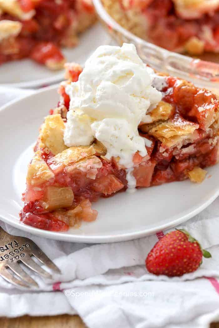 Strawberry Rhubarb Pie on a white plate with ice cream