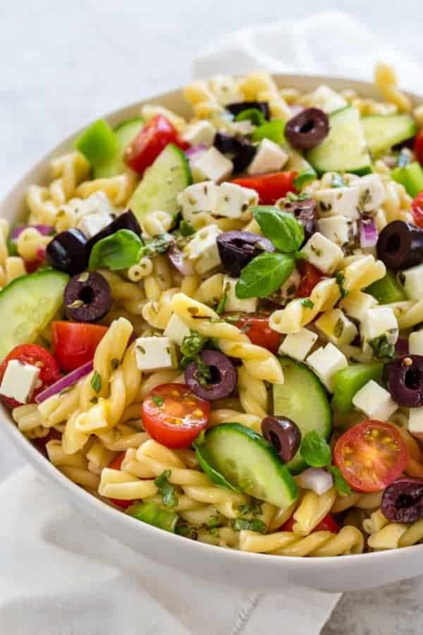 easy greek pasta salad close up in white bowl on white towel