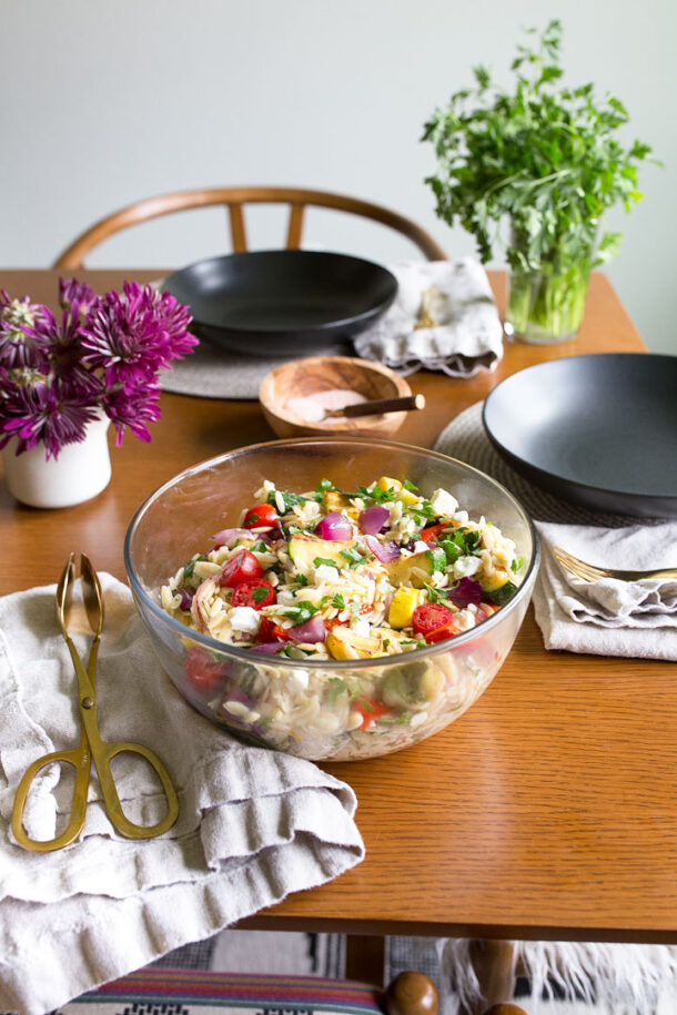 orzo pasta salad with feta on brown table with flowers