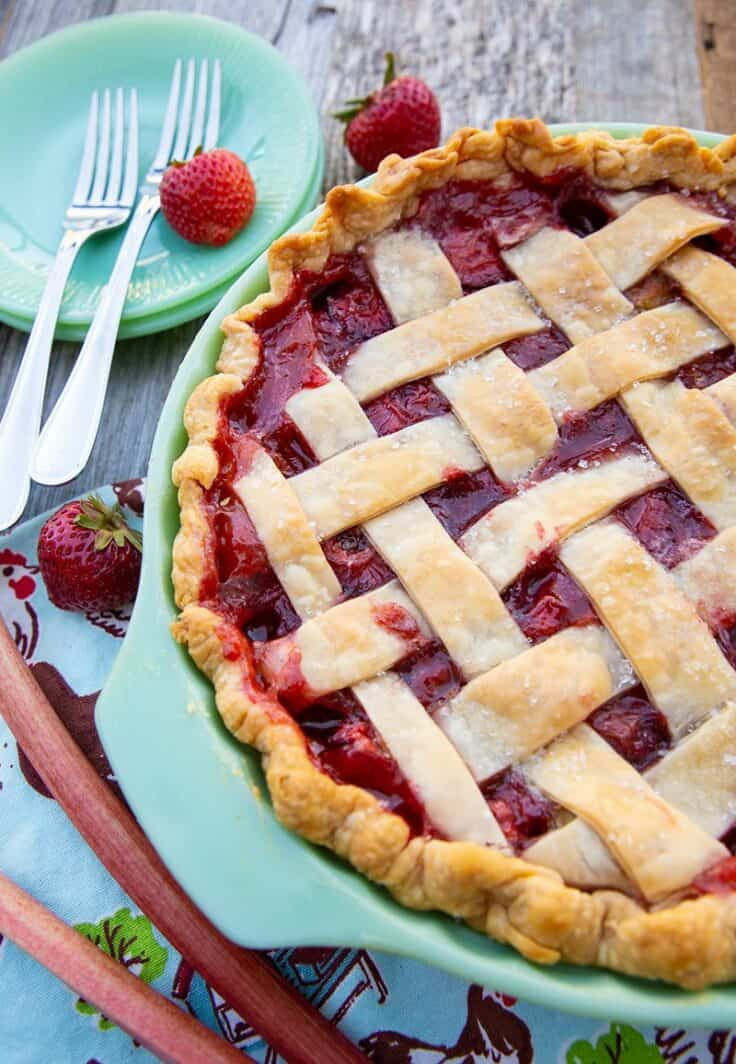 Strawberry Rhubarb Pie in green pie plate with serving plates and forks