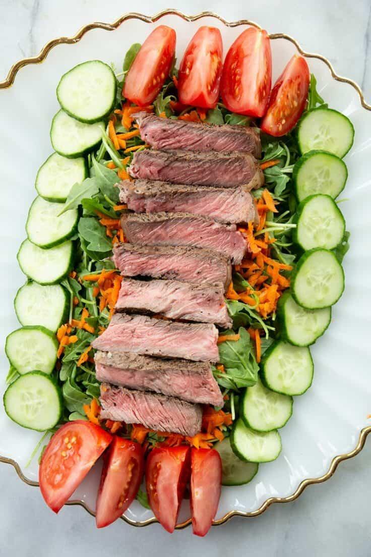 Asian steak salad surrounded by veggies on white platter