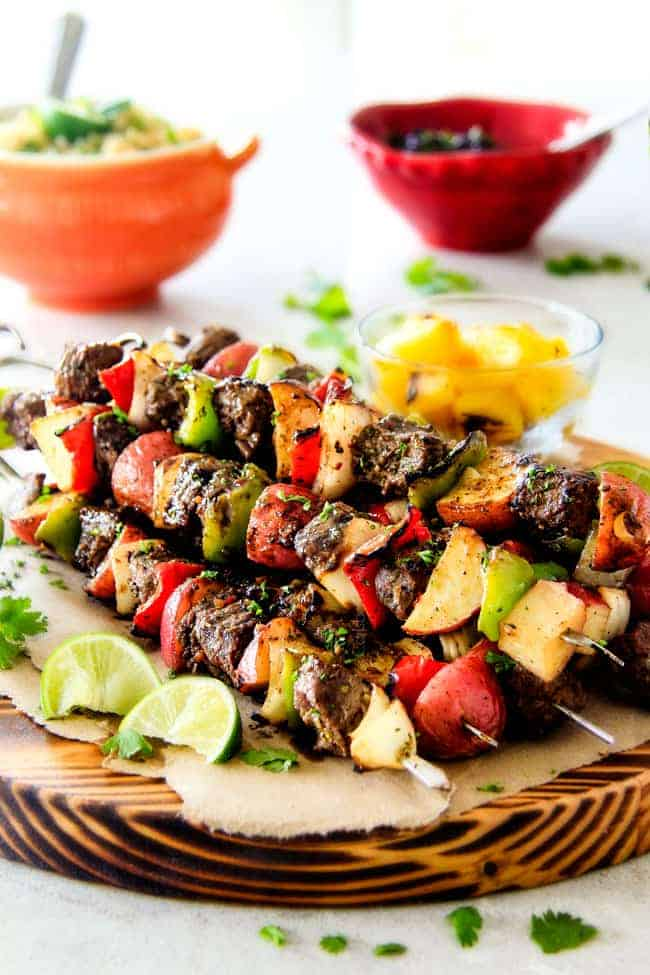 Kabobs on wooden plate with colorful veggies and lime wedges on the side