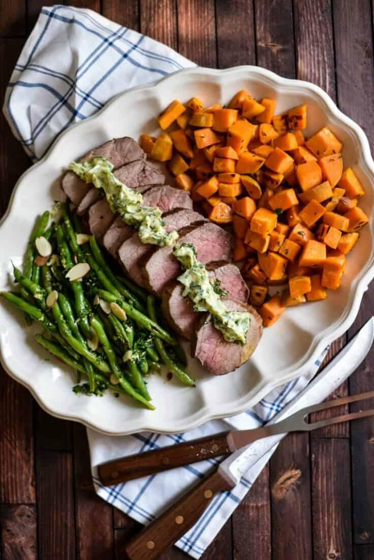 Steak green beans and sweet potatoes on white platter