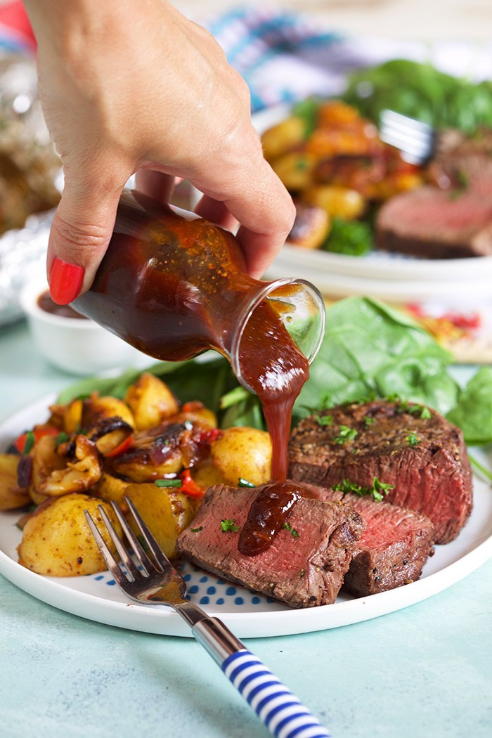 Drizzling sauce on steak on a white plate with fresh greens and potatoes
