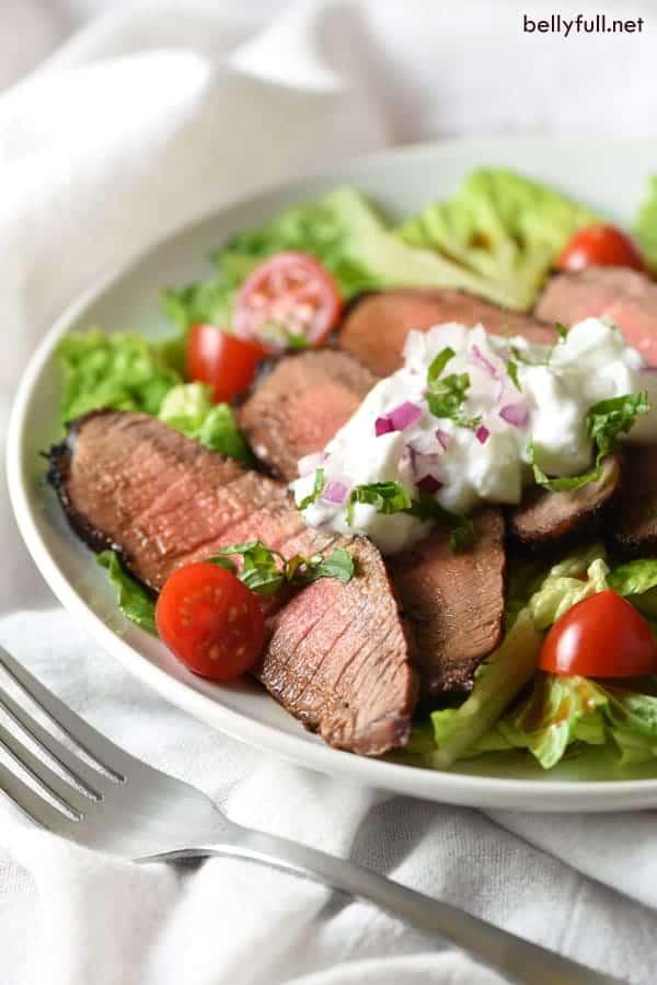 Sliced steak over salad with tzatziki sauce