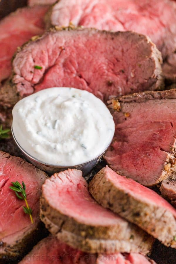 Horseradish sauce surrounded by rare beef cuts close up
