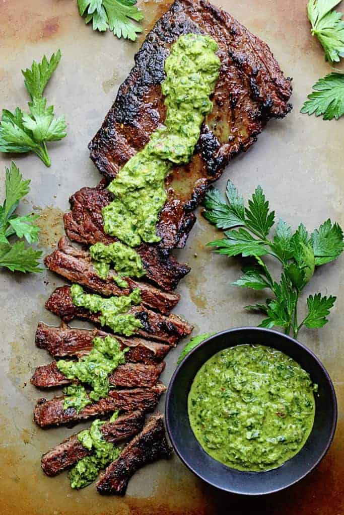 overhead image of Steak sliced with chimichurri sauce