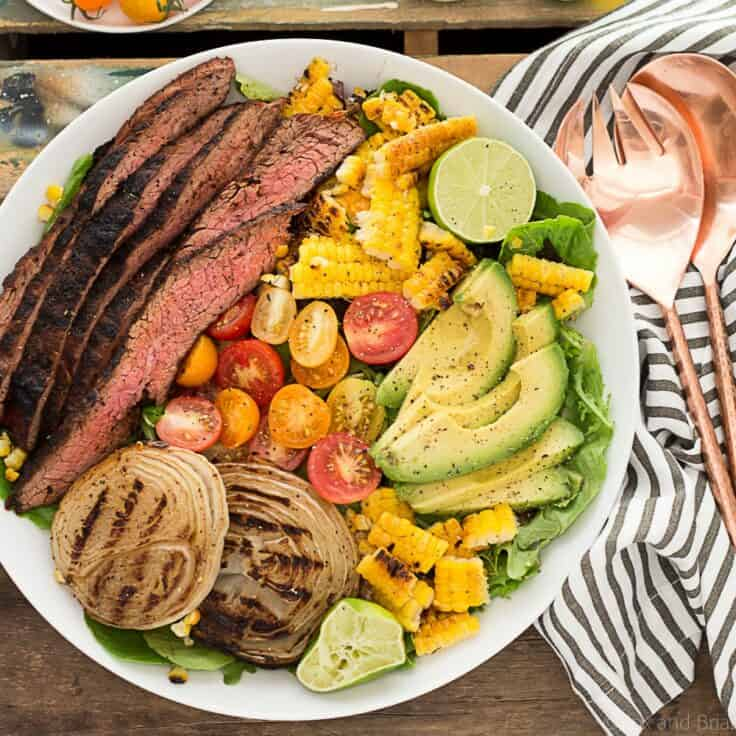Grilled flank steak on bed of mexican veggies on a rustic background