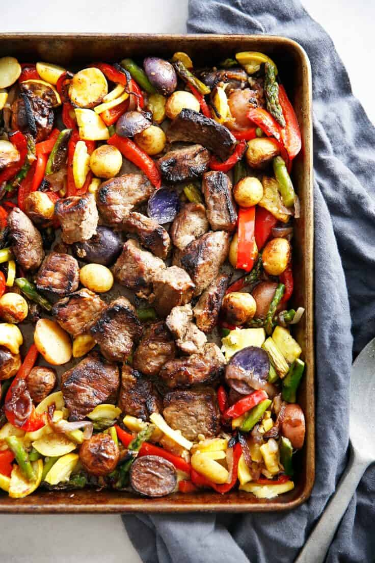 Sheet pan with roasted peppers, asparagus and potatoes with steak and blue towel