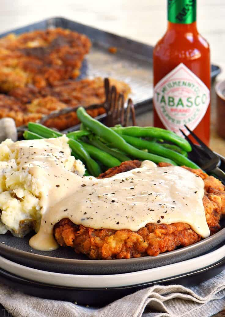 Chicken friend steak with gravy and mashed potatoes and tabasco in the background