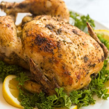 crockpot whole chicken broiled on white plate with lemon and parsley