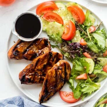 grilled chicken with marinade on white plate overhead