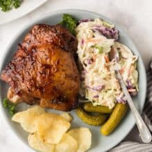 grilled turkey thighs on blue plate with coleslaw pickles and chips