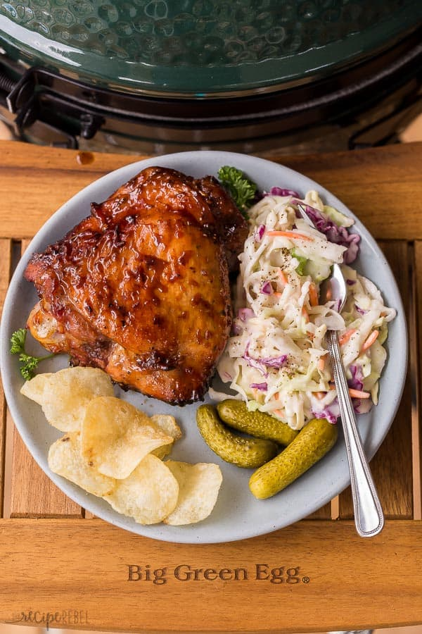 grilled turkey thighs on plate with coleslaw chips and pickles on big green egg