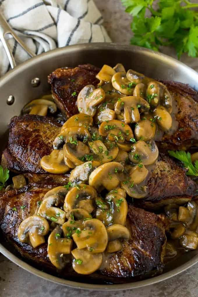 Mushroom sauce on steaks in steel pan with fresh parsley