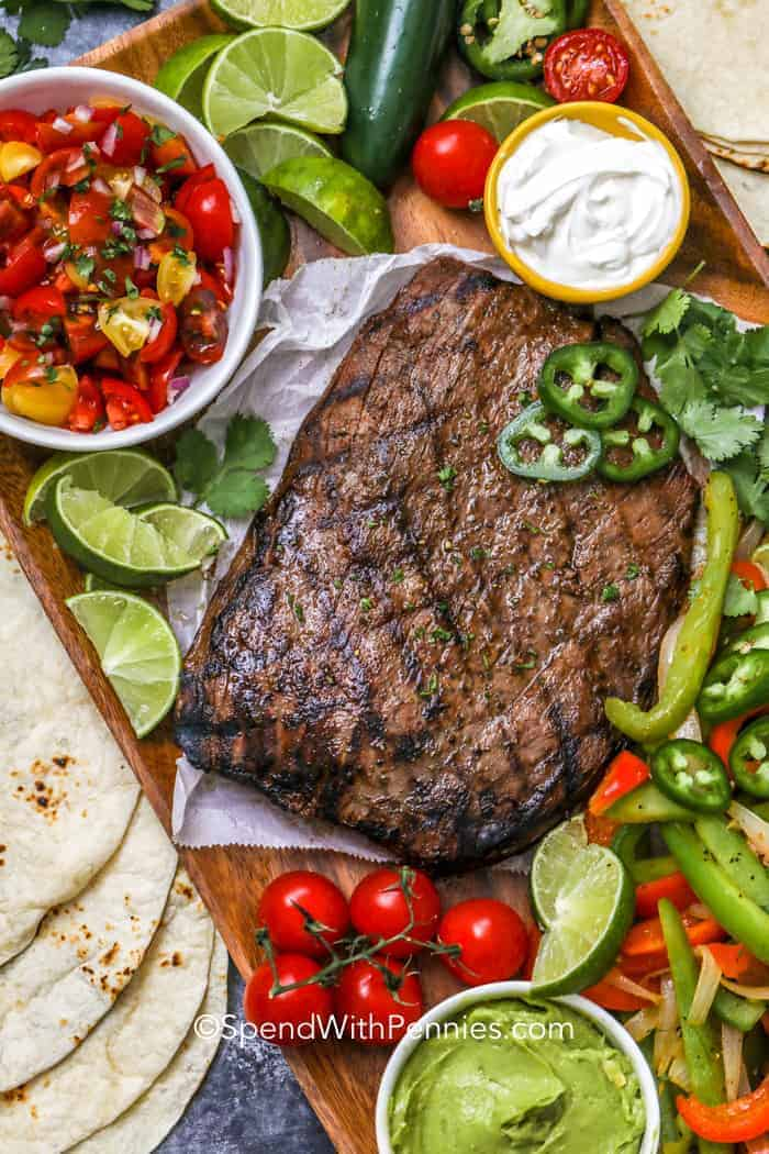 Whole flank steak for fajitas with peppers and lime wedges all around