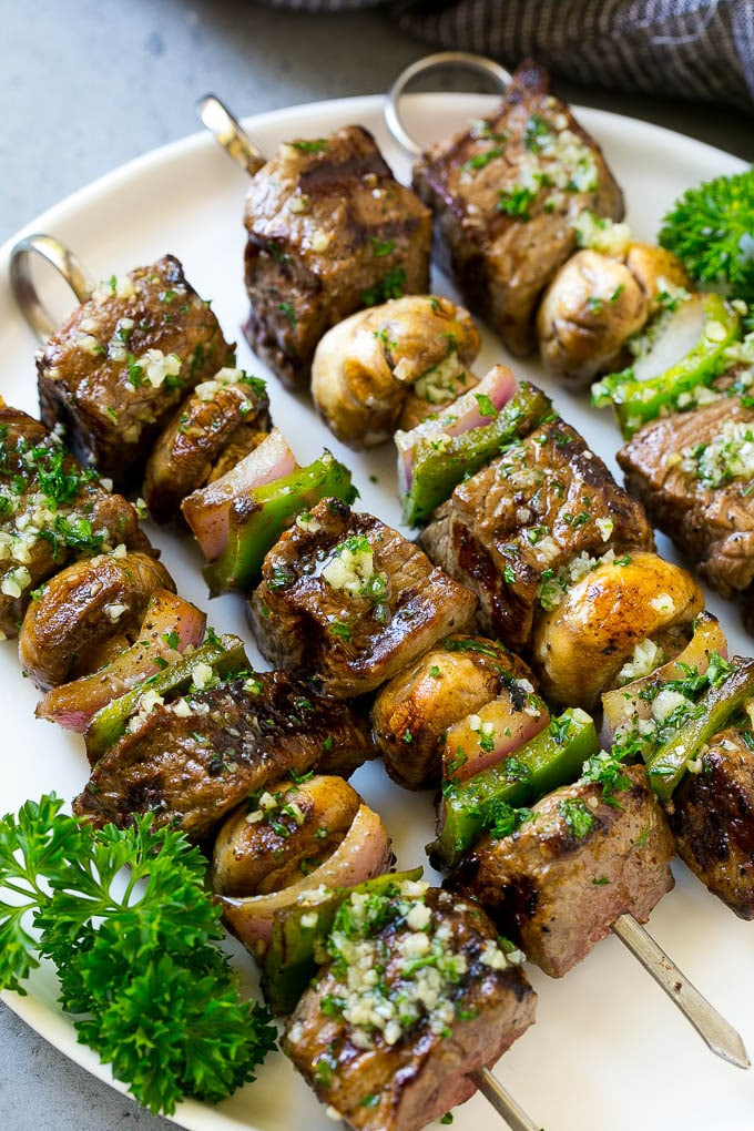 Steak kabobs with grilled veggies and garlic butter on a white plate