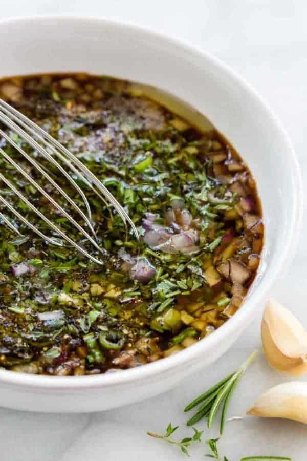 Steak marinade mixed up with whisk and lots of fresh herbs